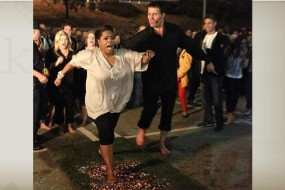 Oprah Winfrey and Tony Robbins walking across hot coals