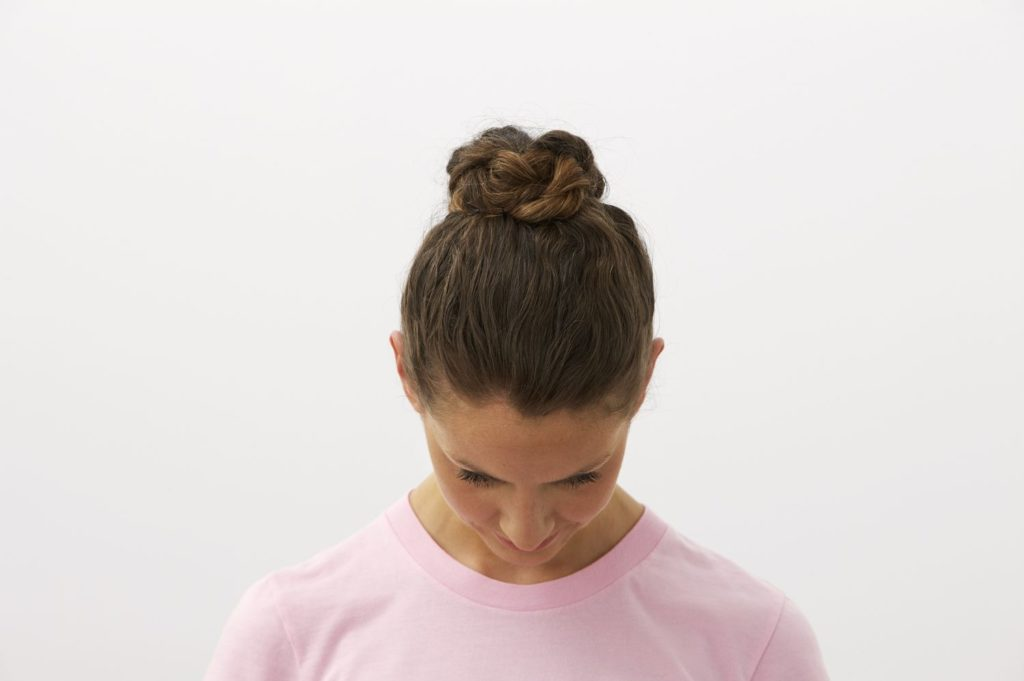 woman-with-head-down-showing-hair-bun-awaken