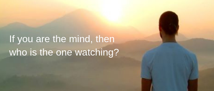 Guy meditating and looking out over the hills.