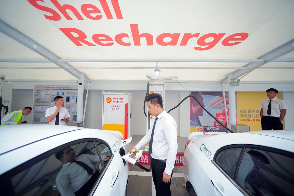 A worker charges an electric car at a Shell charging station on September 28, 2018 in Tianjin,