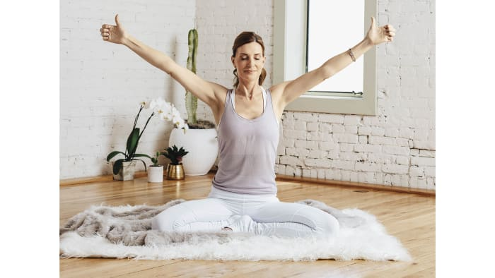 Take a comfortable seat, keeping your spine long. For 1 minute, close your eyes, and begin observing the flow of life force (prana)with each breath in and out. Then, curl your fingers so that your fingertips touch the pads of your palms, just below each finger. Extend your thumbs away from your palms, and stretch your arms up from your shoulders so they form a wide V shape. Keep your elbows locked and your arms straight, elongating the distance from your heart to the tips of your thumbs. Hold this position and start Breath of Fire (rapid inhalations and exhalations through your nose) for 3 minutes. When you are finished, deeply inhale while stretching your arms straight up overhead with the tips of your thumbs pressed together. Suspend your breath, and apply Mula Bandha (Root Lock) by contracting your rectum, navel, and sex organs. Stretch your spine up from your pelvis. As you exhale, extend your fingers with your palms facing down, and sweep your arms out and around you, visualizing light coming out of your fingertips. Comb through your aura with your fingers, removing toxicity and negativity. As you clear the negative energy with your hands, imagine you are releasing it down into the earth below you. To finish, lower your hands onto your thighs with palms facing up. Feel your energy circulating out into your aura. Visualize the pure and beautiful light you have created.See also Kundalini 101: A Practice for Finding Instant Calm