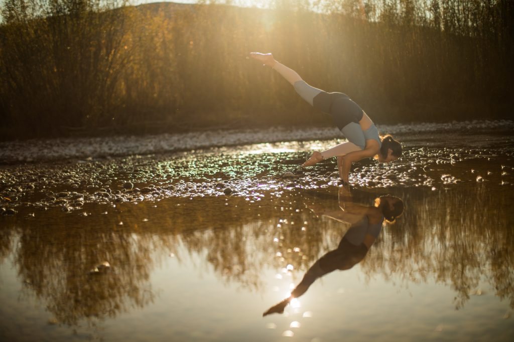 woman practices yoga near a reflective pond -yogatoday