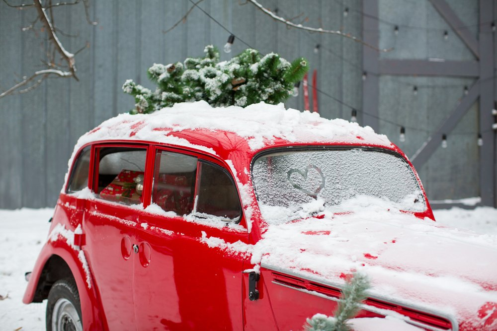red retro car with a Christmas tree on top and presents