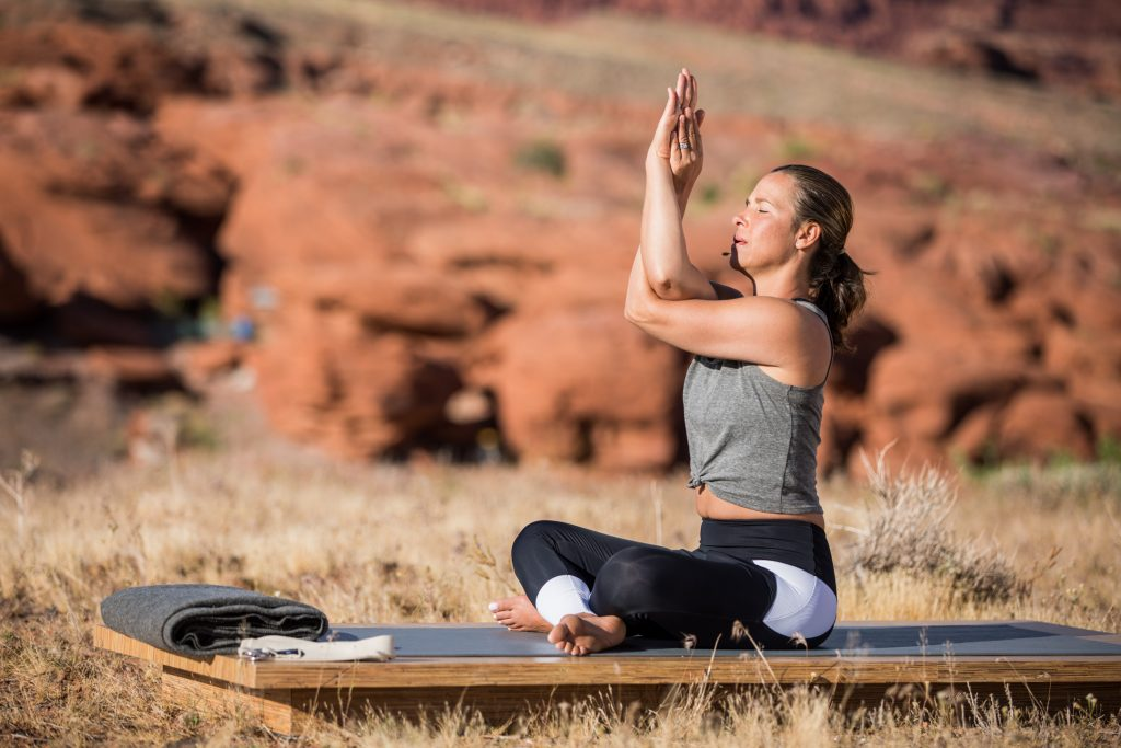 woman practices eagle pose to stretch her shoulders - yogatoday