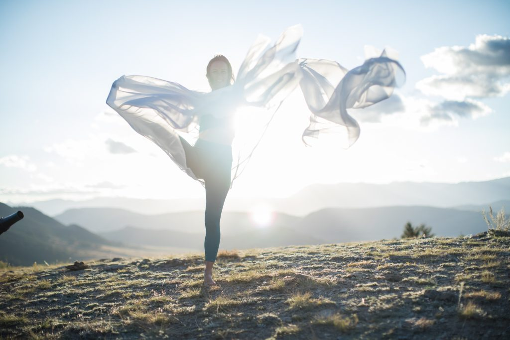 woman practices yoga draped in a white scarf -yogatoday