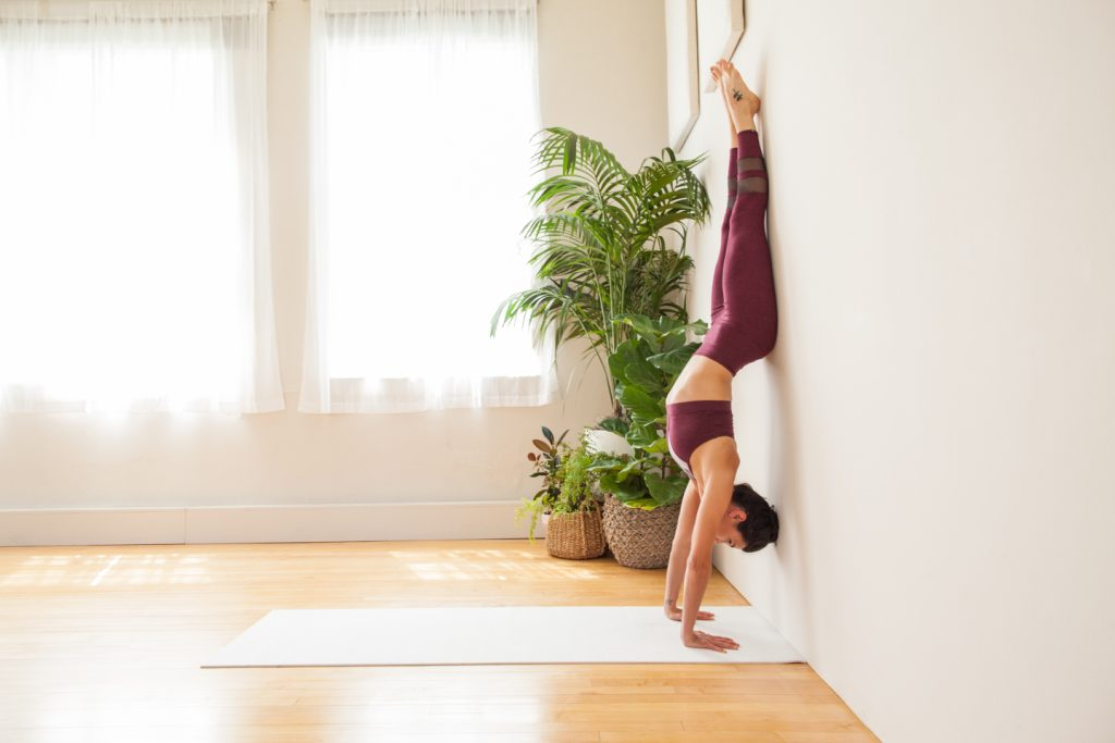 woman practices a handstand against a wall in her home