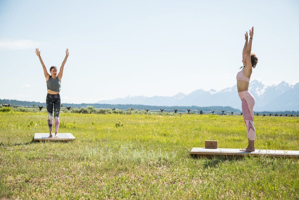 yoga teacher and student practice sun salutations -yogatoday