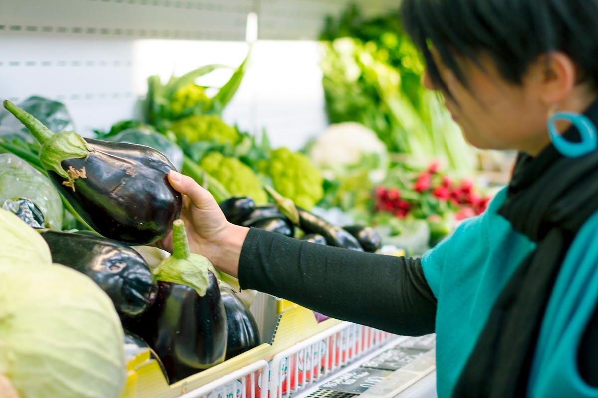 woman choosing eggplants
