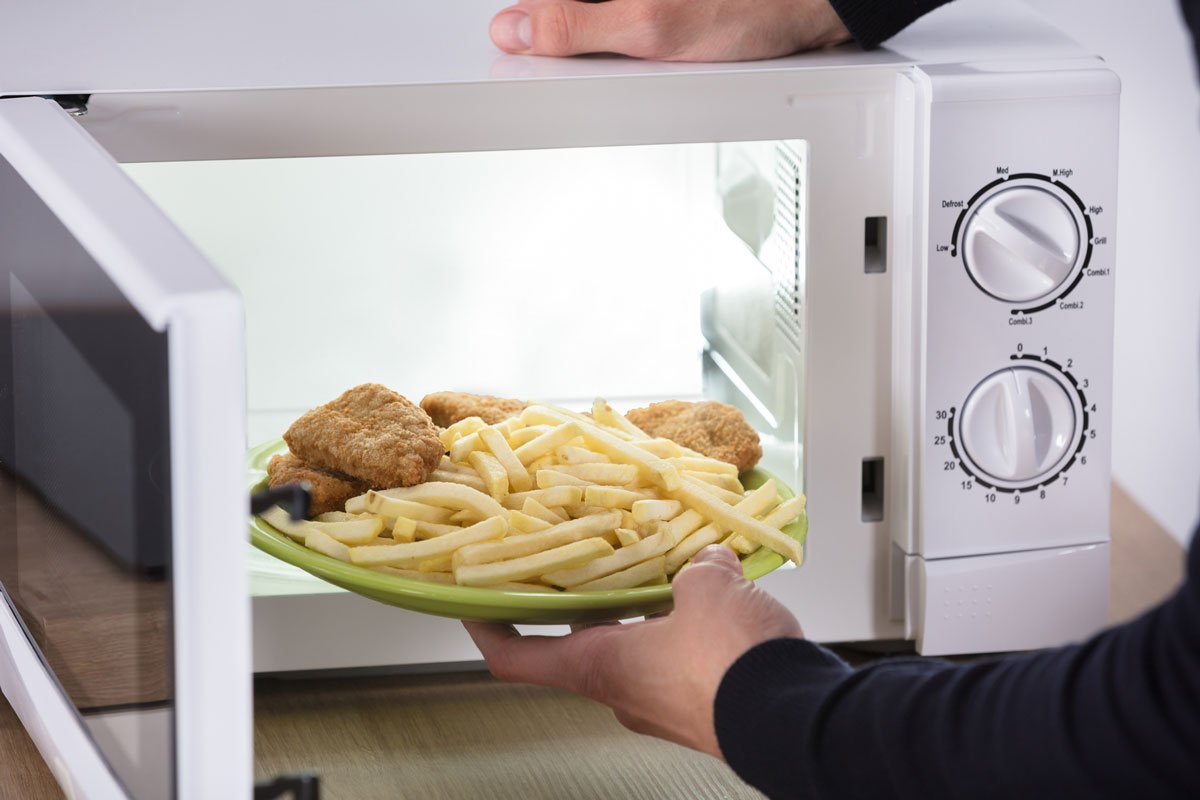 fries and battered chicken being placed in microwave