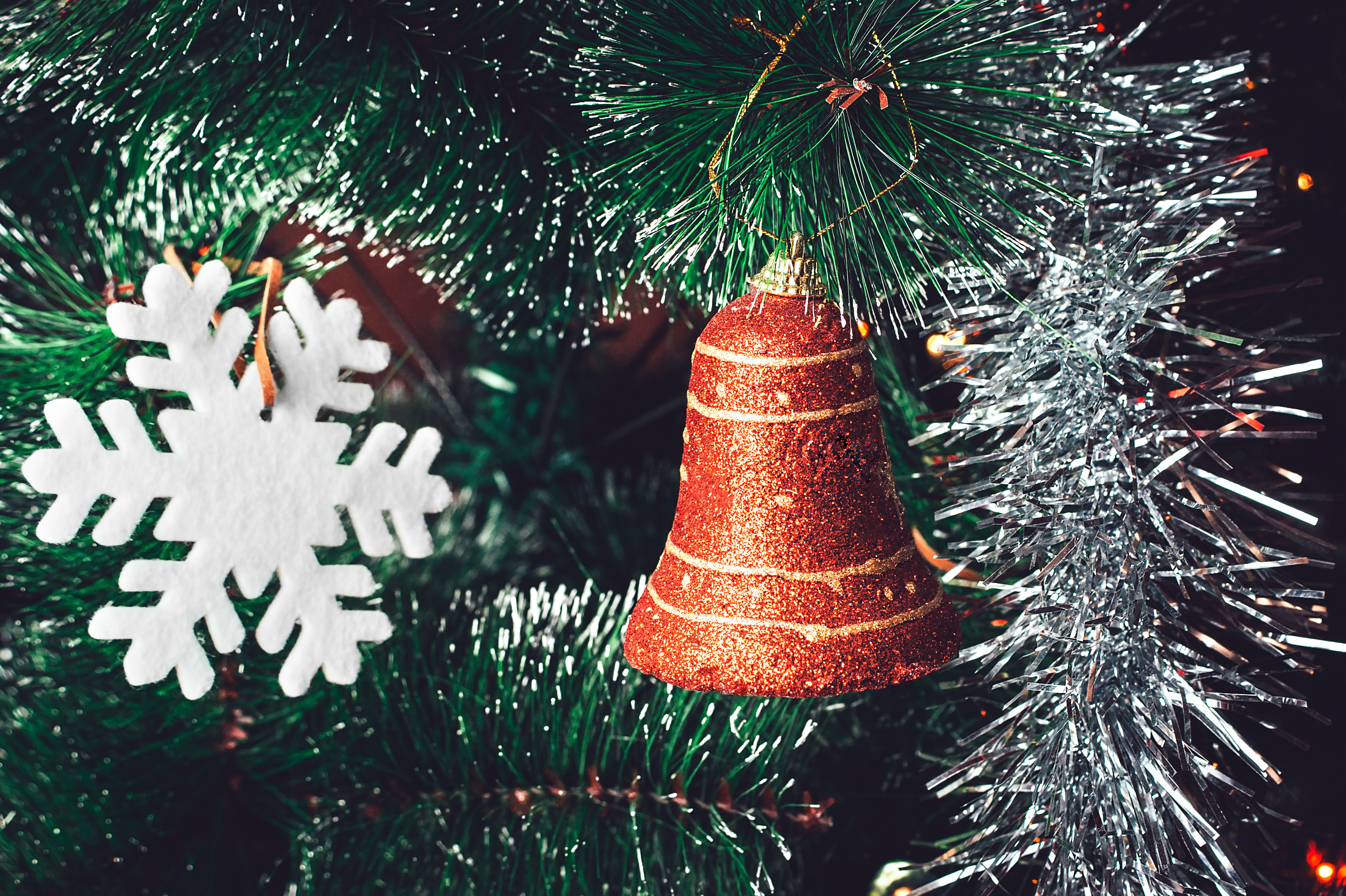 Christmas Tree Decorations: Red Orange Bell, White Snowflake, Shining Silver Tinsel on Green Needles with White Tips. Happy New Year and Christmas Concept.