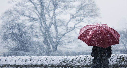 woman-sheltering-under-umbrella-in-a-snow-storm-awaken